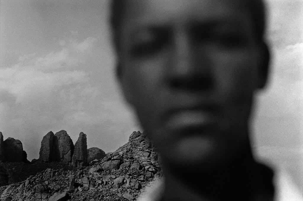 Sidi, environ 17 ans, n'a jamais été scolarisé. Il vit dans un campement semi-nomade avec sa mère, sa sœur Sekiwa, et un frère qui vient de naître. Son père travaille à Djanet et ne revient qu'une ou deux fois par mois. Oued Essendilène, Tassili n'Ajjers, 1997