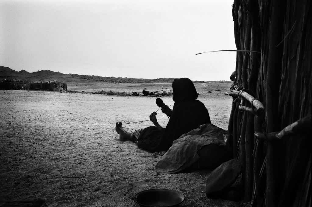 A la fraîche dans le village de Touaregs sédentaires dEzarnen, une vieille femme file des poils de chèvre. Tassili n'Ajjers, Sahara algérien, 1993