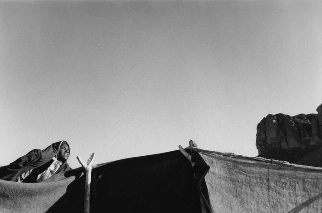 Dans le campement de sédentaires dans l'Oued Elt, une jeune Touarègue sort de sa tente vers 6h pour regrouper chèvres, ânes, moutons en vue du trajet quotidien dans le désert vers la guelta Tuya. La destination est toujours la même mais les trajets varient afin que la végétation dont se nourissent les animaux ne soit pas épuisée. Tassili n'Ajjers, 1993