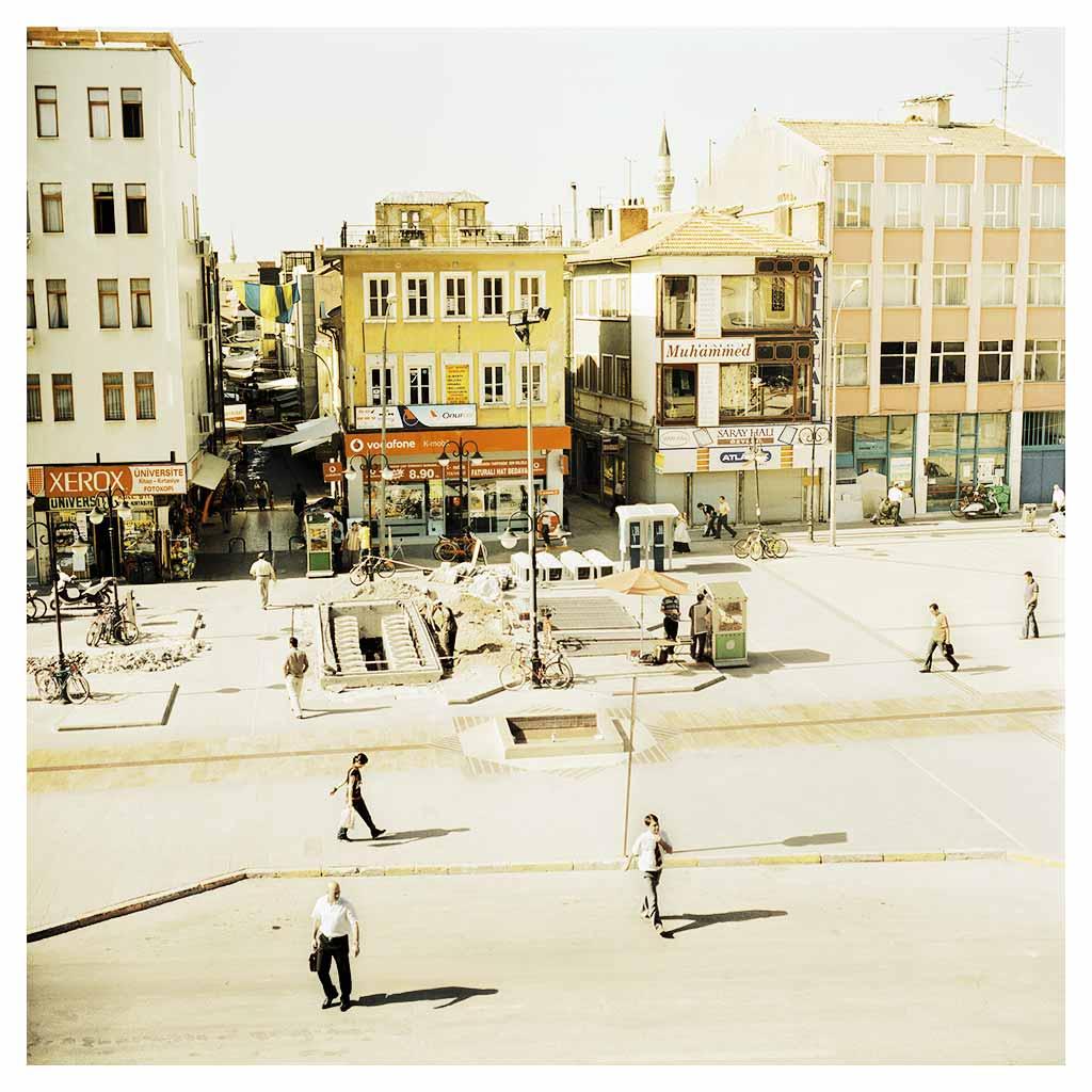 """Vue sur Hükümet Meydani (""""la place du Gouvernement) situé dans le vieux centre de Konya, avec les bâtiments disparates et les allées où le soleil ne pénètre pas, si typiques du tissu urbain traditionnel, à l'échelle humaine.  Cette place, et derrière elle, les allées du bazar de Konya, sont un havre pour les piétons dans une ville où les véhicules sont toujours plus intrusives.  Hukumet Meydani (""""Government Square"""") in the old, central part of Konya with the usual disparate buildings and shaded alleyways typical of traditional, human-scale urban fabric.  The square and behind it, the bazaar section of Konya, are a pedestrian haven in a city where motor vehicles are increasingly intrusive."""