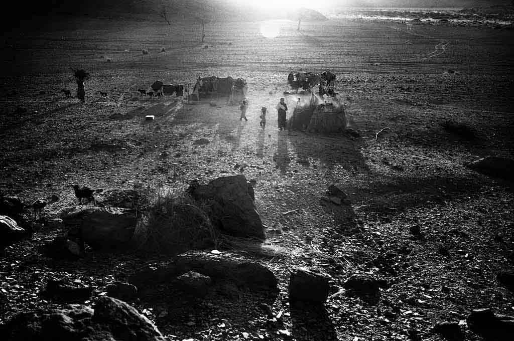 Début de soirée dans le campement semi-nomade dans l'Oued Elt. Les femmes sont allées chercher du bois dans le désert alentour pour préparer le repas du soir. Tassili n'Ajjers, Sahara algérien, 1997
