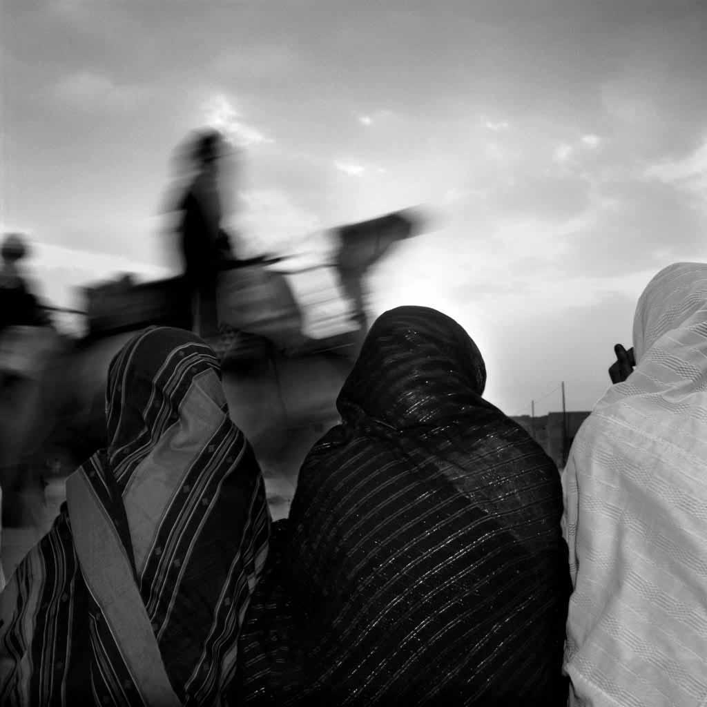 """Les fêtes de mariage permettent de sortir de la monotonie de tous les jours. Les femmes admirent en poussant des """"youyous"""" les hommes qui paradent sur leur chameau, fiers. Tamanrasset, Tassili du Hoggar, 1993"""