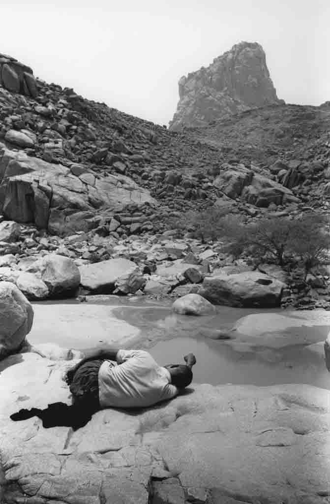 Ce Touareg sédentarisé du village d'In-dalag mène chaque jour paître son troupeau de chèvres qui comprend quelques moutons. Au plus chaud de la journée, lui et ses bêtes se reposent autour du point d'eau. Tassili du Hoggar, Sahara algérien, 1991