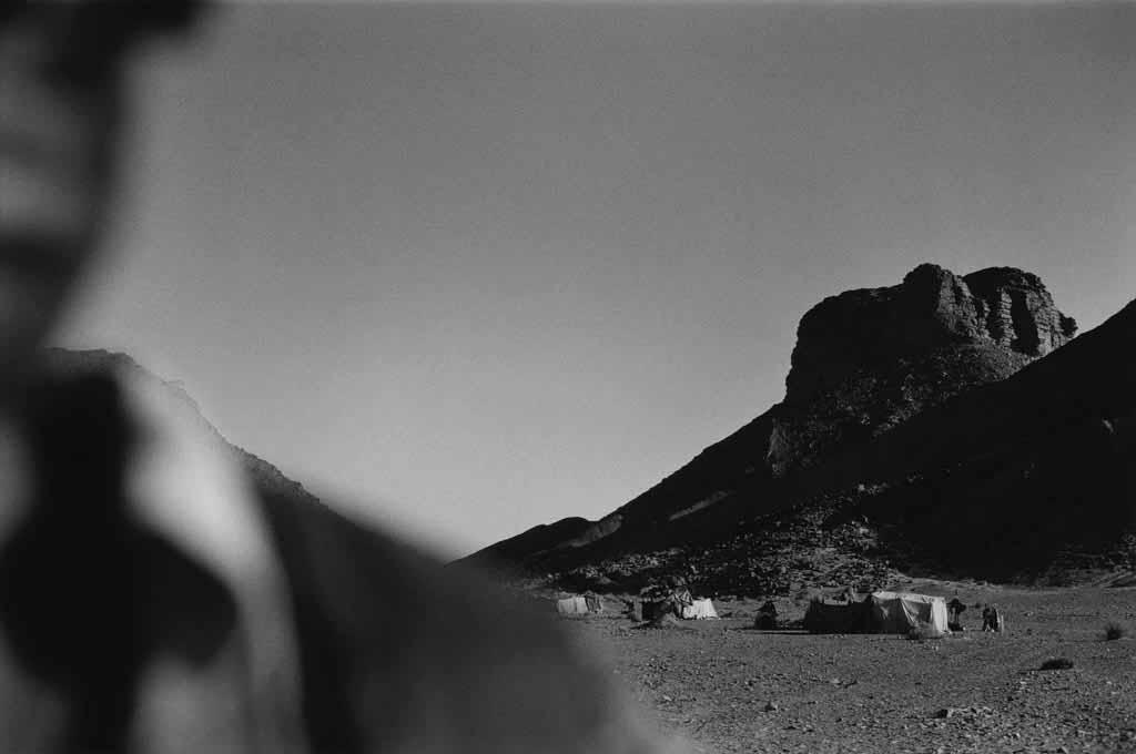 Mohammed, jeune homme de 27 ans, vit et travaille dans l'oasis de Djanet. Il revient souvent dans le campement semi-nomade de six tentes où habite encore sa mère. Oued Elt, Sahara algérien, 1997