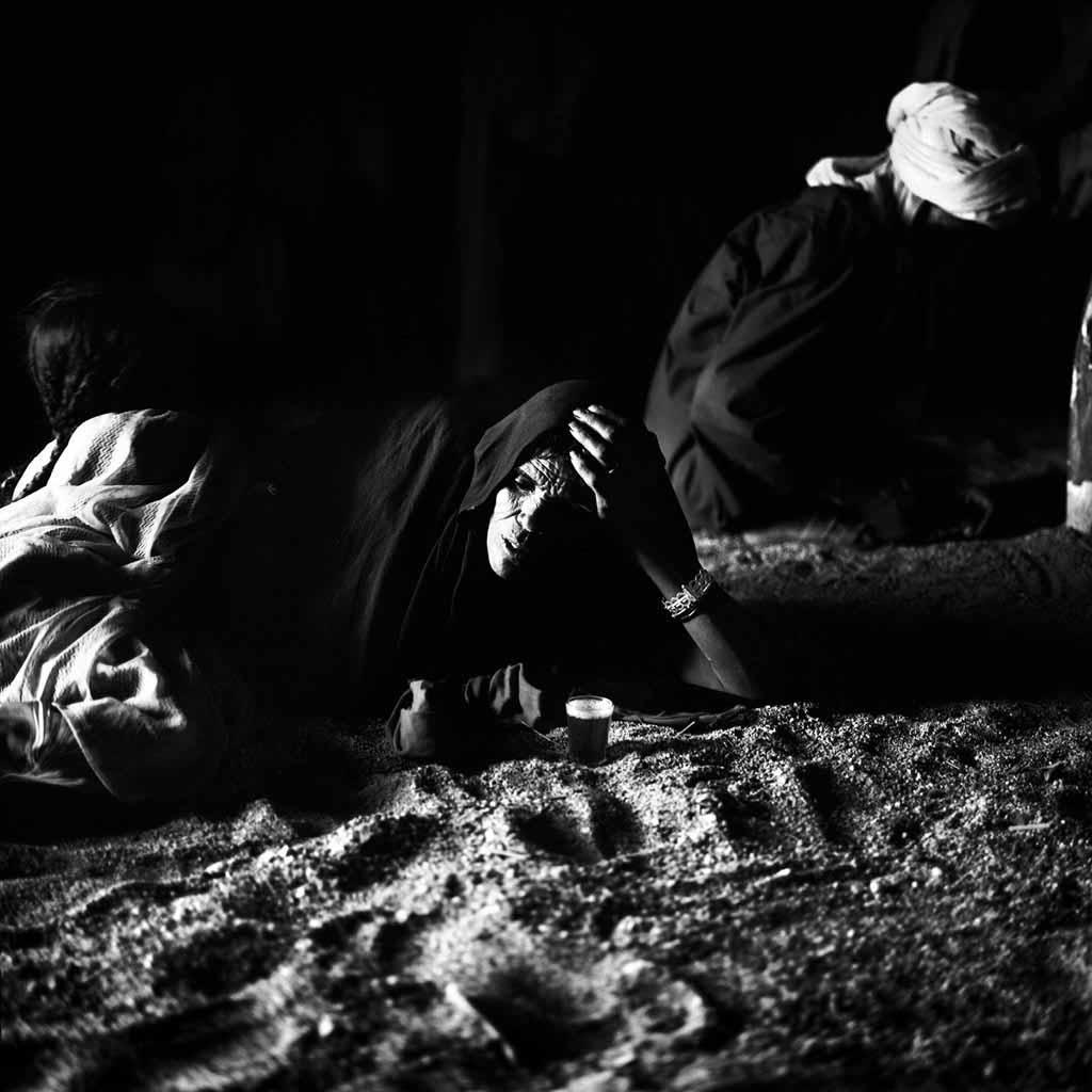 Dans le village de Touaregs sédentaires, Ezarnen, une famille se repose en fin d'après-midi avant de reprendre leurs tâches respectives. Tassili du Hoggar, Sahara algérien, 1993
