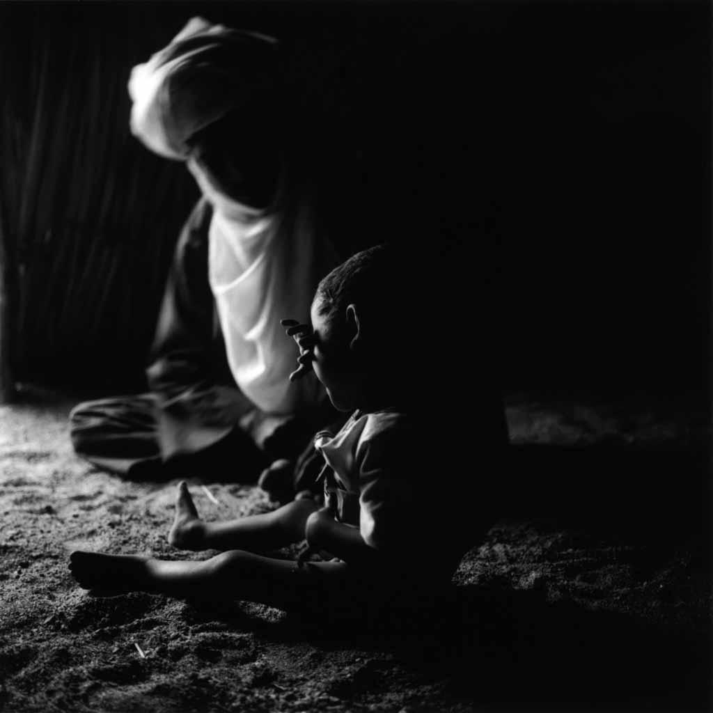 Le petit Mohammed est contrarié. Il pleure en se cachant derrière son bras. Son père, Entayent, essaie de le consoler par l'humour. Ezarnen, village de Touaregs sédentaires, Tassili du Hoggar, 1993
