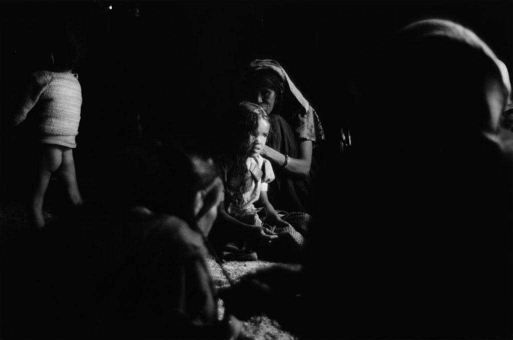 Les femmes et filles d'Ezarnen se sont réunies dans l'akabar de Raïcha. Demain, c'est l'Aïd. Les femmes se sont lavées au point d'eau dans le désert et sont en train de se coiffer mutuellement. Raïcha coiffe sa plus jeune fille. Tassili du Hoggar, Sahara algérien, 1993