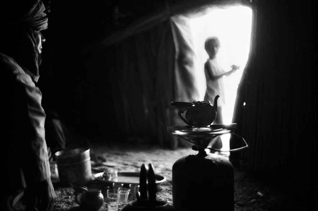 Dans le village de Taroumout, à 40 km de Tamanrasset, c'est l'heure du thé. Les trois verres de thé - amer, peu sucré, sucré - sont pris dans l'après-midi lorsque la chaleur a un peu diminué. Tassili du Hoggar, Sahara algérien, 1993