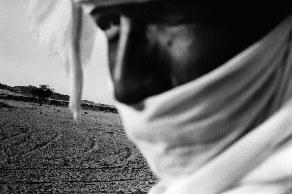 Atayeb partage sa vie entre la ville de Djanet et un campement semi-nomade dans l'Oued Essendilène où habite encore sa famille. Il fait le chemin entre Djanet et le campement encore à chameau, alors que beaucoup de Touaregs ont abandonné les chameaux pour les 4x4. Sahara algérien, 1997